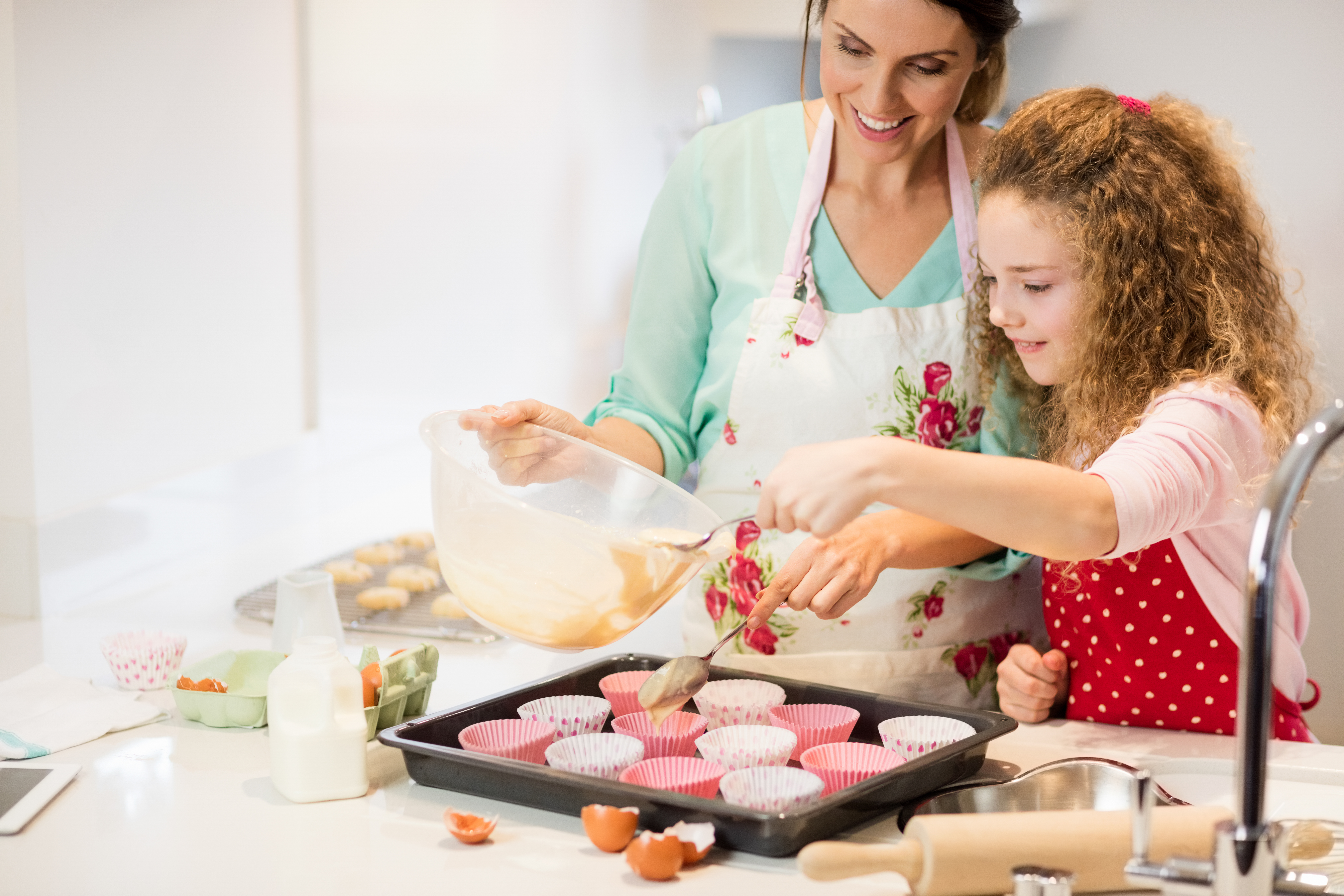 Mother and daughter preparing cupcake in kitchen